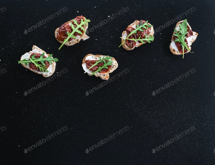 Bruschettas with dried tomatoes, arugula and smoked meat over a