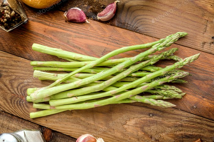 green asparagus without cooking, on rustic wood