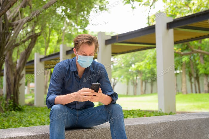 Young man with mask using phone and sitting at the park