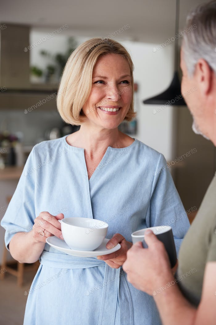Senior Couple Standing At Home In Kitchen Drinking Morning Coffee Together
