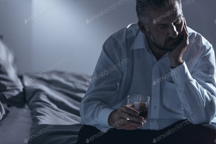 Close-up of a man with midlife crisis sitting on a bed with one