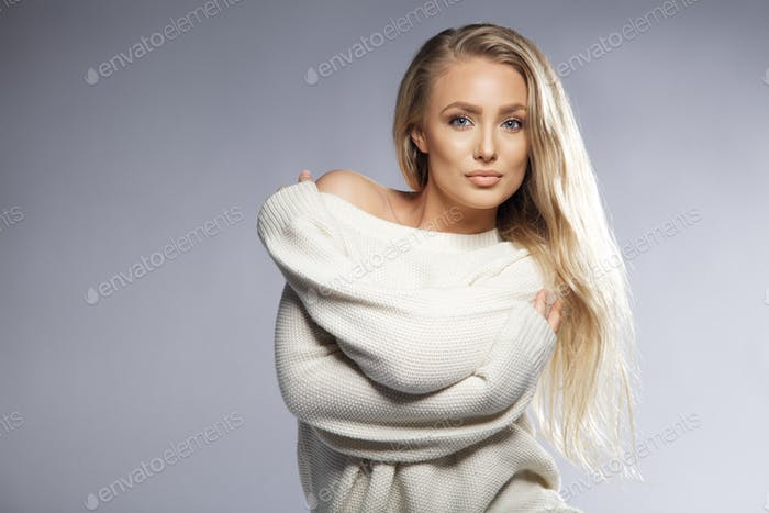 Sensual young woman posing in oversized sweater