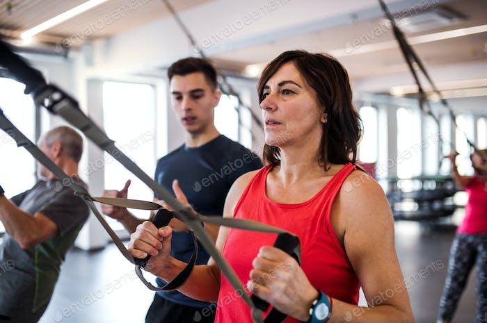 Eine Gruppe von fröhlichen Senioren im Fitnessstudio mit einem jungen Trainer macht Übung mit TRX.