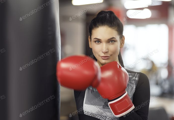 Personal defense class. Young female boxer in gym