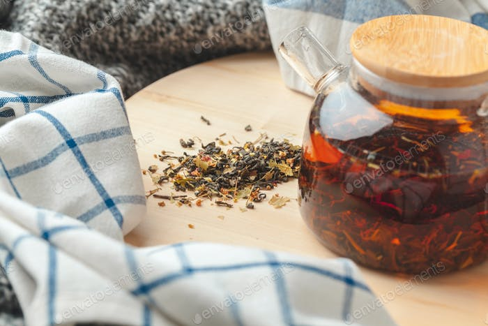 Earl Grey tea in glass tea pot on wood plate close up