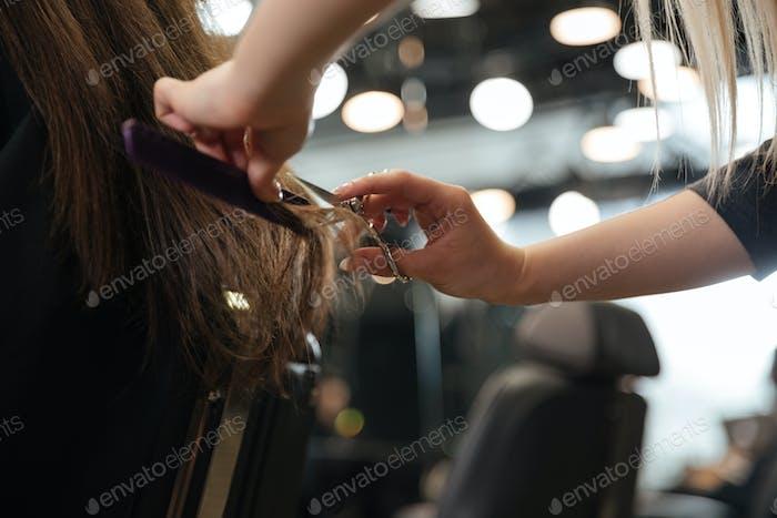 Профессиональный парикмахер делает стильную стрижку