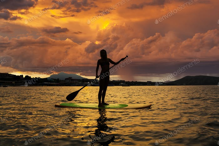 Silhouette of a girl on Stand Up Paddle Board on the background
