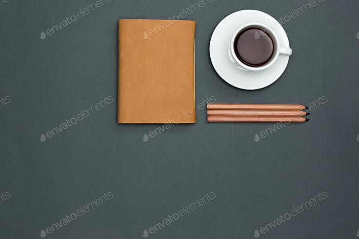 Office desk table with pencils, notebook and a cup of coffee