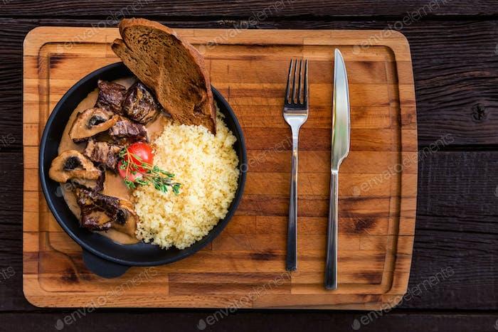 Draufsicht Pilzrindfleisch Stroganoff in Bratpfanne mit Couscous
