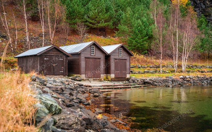 Three wooden huts on the shore of a fiord
