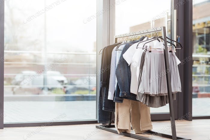 Various clothes on hager at shop interior against window