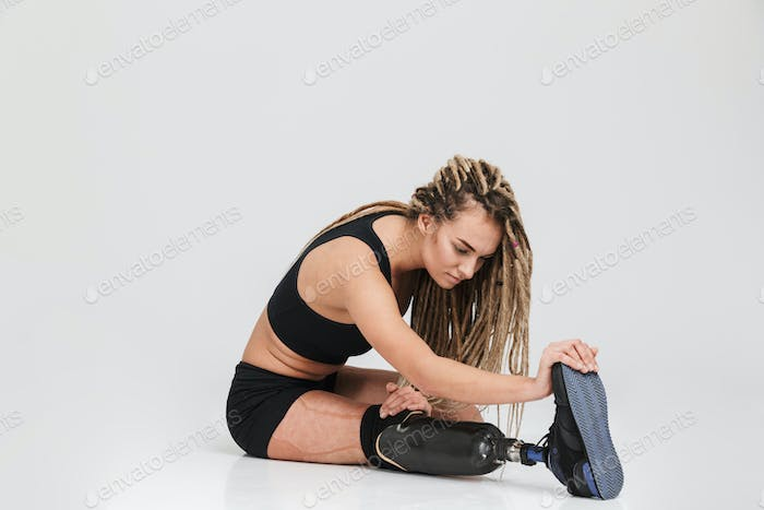 Healthy young disabled sportswoman make stretching exercises.