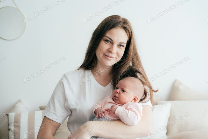 Beautiful young redhead freckled mom holds and hugs a newborn month old baby.