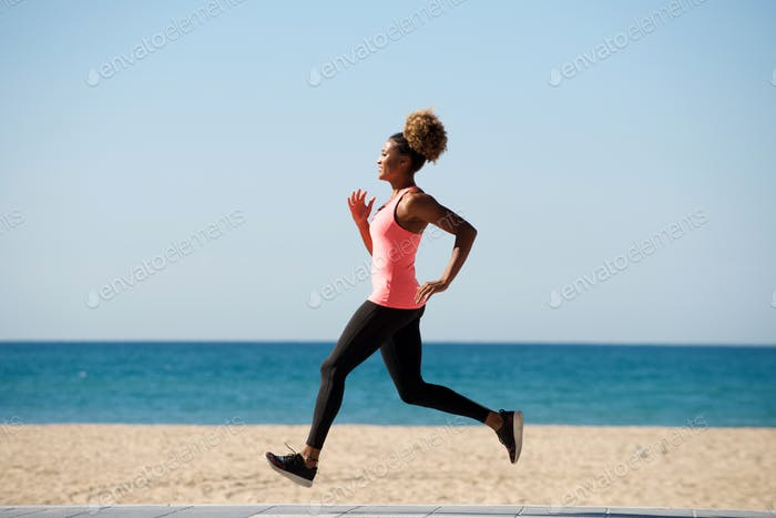 Full length healthy african woman running along the beach in morning