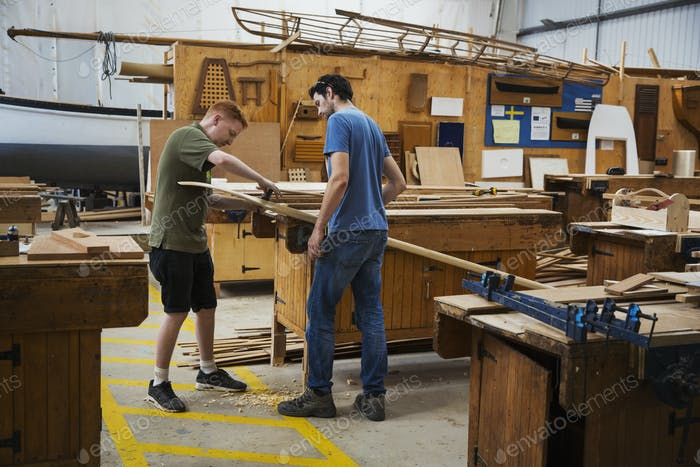 Two men standing at a workbench in a boat-builder's workshop, working on piece of wood.