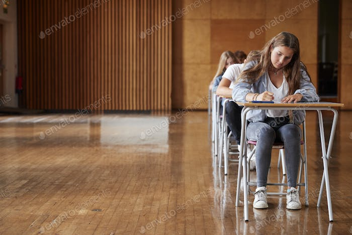 Group Of Teenage Students Sitting Examination In School Hall