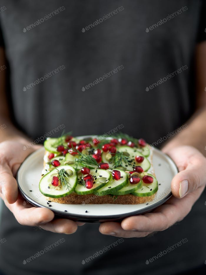 Vegan sandwich with cucmber in male hands