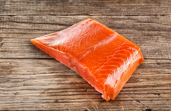 Salmon steak on wooden background. Close-up.