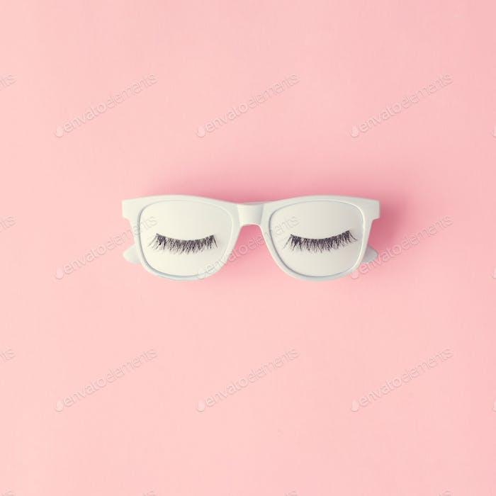 Creative layout made of white painted sunglasses and eyelashes on pastel pink background.