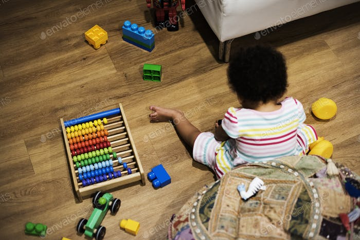 Brazilian toddler girl playing wooden toys on the floor