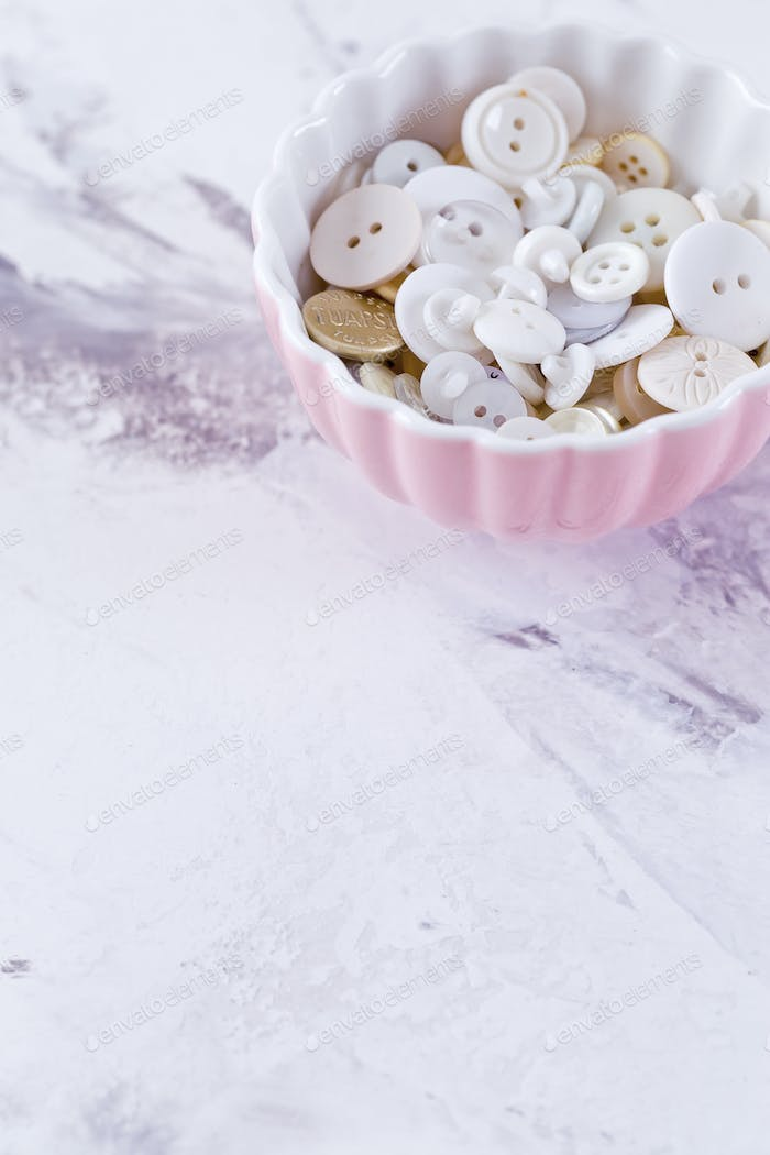 Pink Bowl with white buttons over marble table