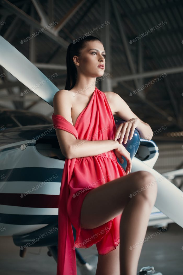 Beautiful fashion model pilot girl in a red dress posing next to propeller plane in the garage