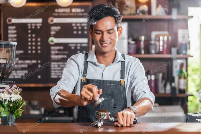 Asian Barista tamping the portafilter and preparing cup of coffee, espresso with latte