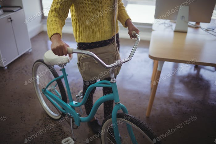 Low section of businesswoman with bicycle office