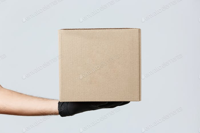 Kontaktloses Ausliefern, covid-19 und Einkaufskonzept. Bild der Kurierhand in Gummihandschuhen