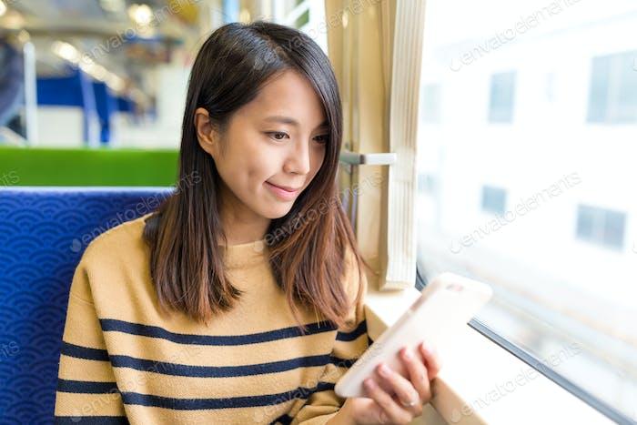 Молодая женщина работает на мобильном телефоне в поезде