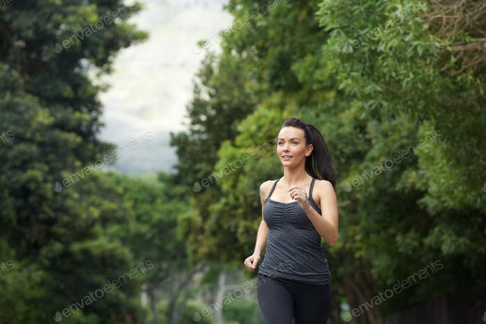 Confident young woman running outdoors