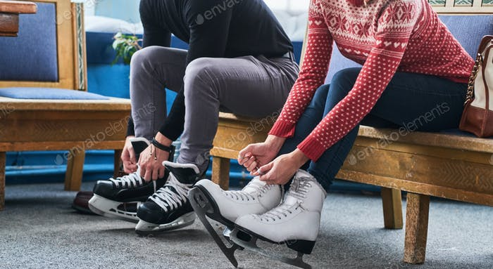 Young couple sitting on a bench and tying shoelaces of ice hockey skates in the locker room