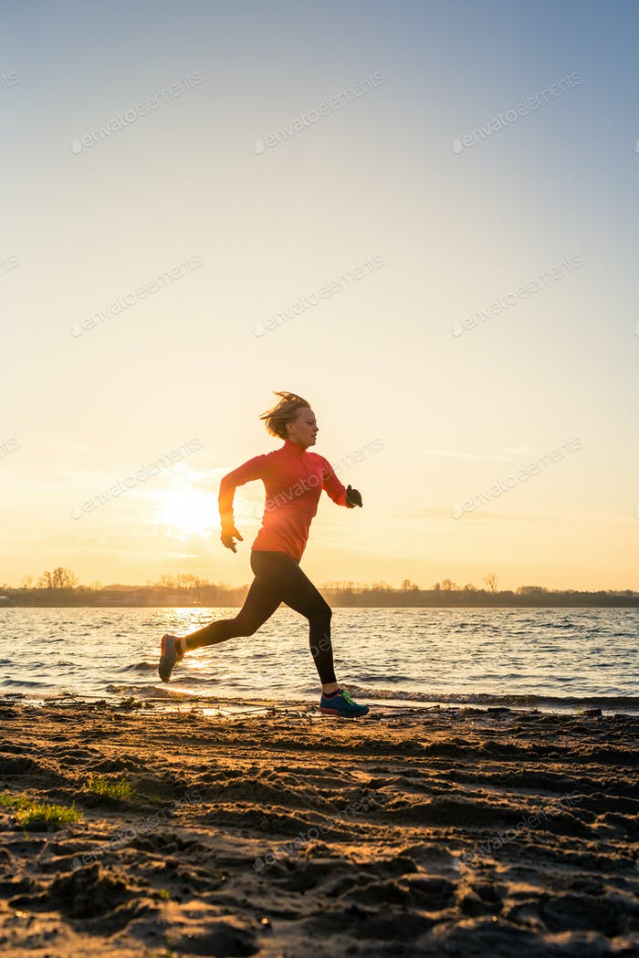 Beach jogging at sunrise, lake coastline