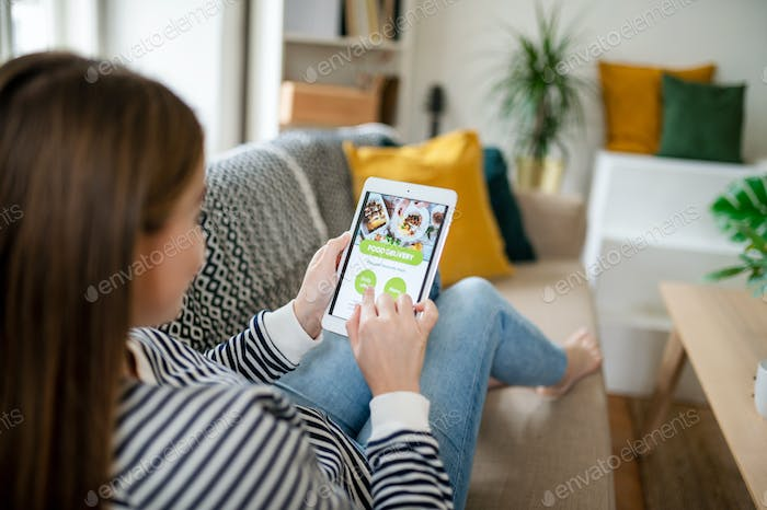 Young woman with smartphone ordering food at home, coronavirus and food delivery concept.