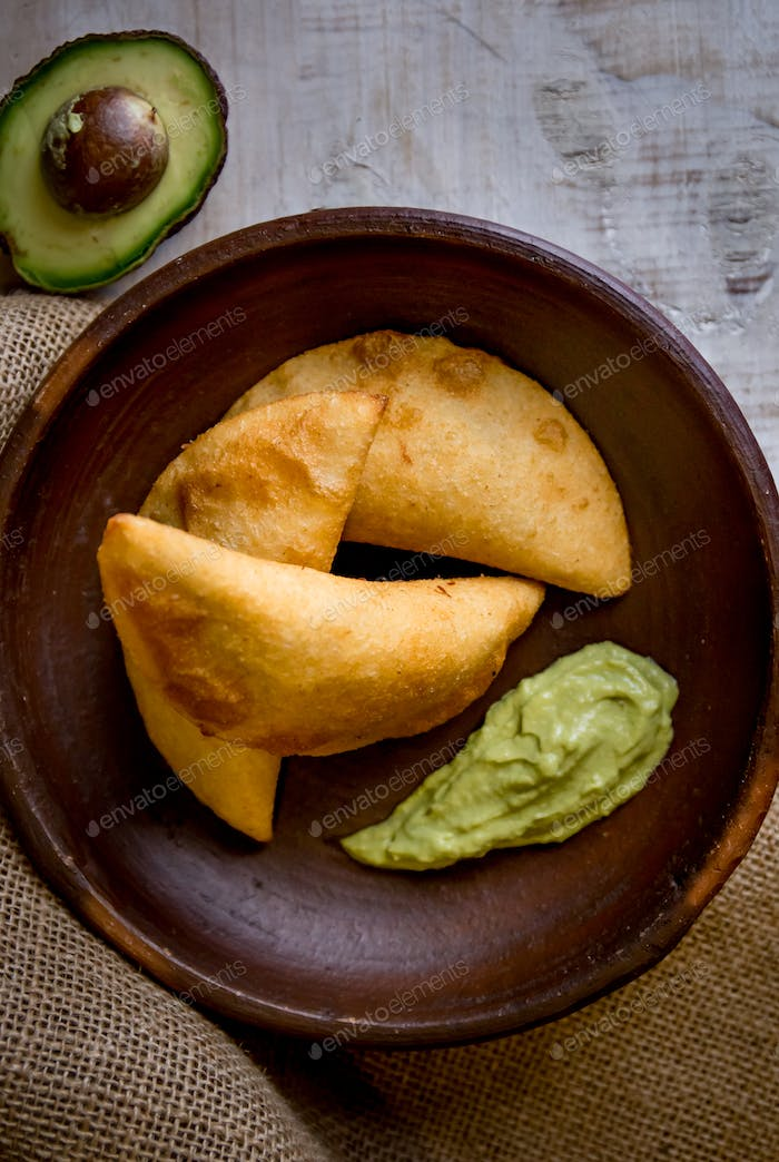 Venezuelan typicals corn empanadas with meat in clay bowl with avocado sauce.