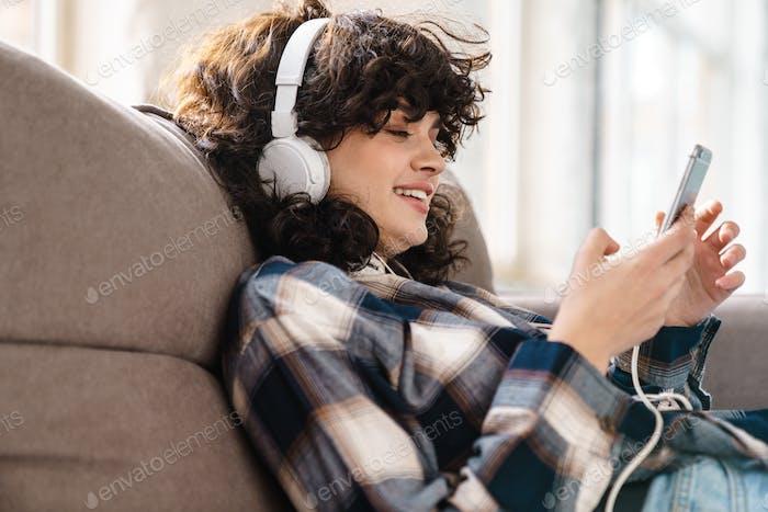 Joyful beautiful curly girl in headphones using cellphone and smiling
