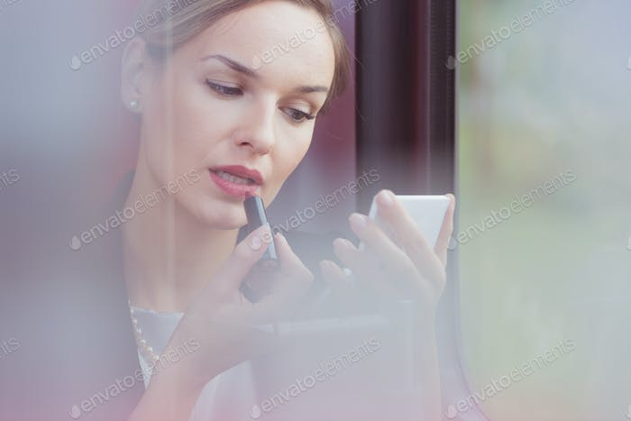 Businesswoman improving her make up