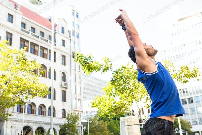 Schöner Athlet Stretching vor Gebäuden in der Stadt