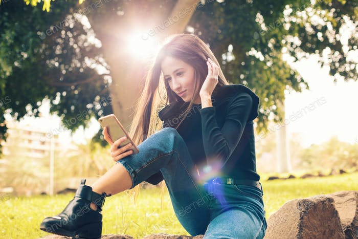 Young woman using smartphone in park