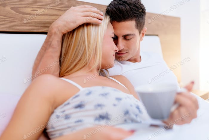 Couple in love drinking morning coffee in bed