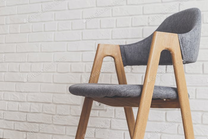 Modern grey chair with white brick walls on background