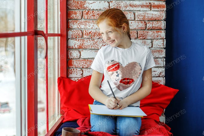 Happy child is a teenager sitting on a window sill and drawing.