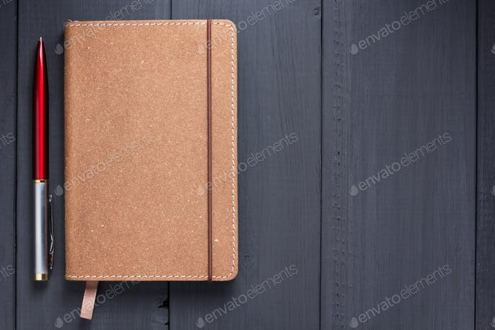 notepad and pen at black wooden background surface table