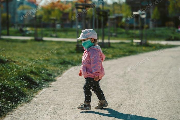 young girl with mask outdoor, coronavirus epidemic