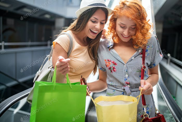 Women friends with shopping bags having fun while shopping in a mall