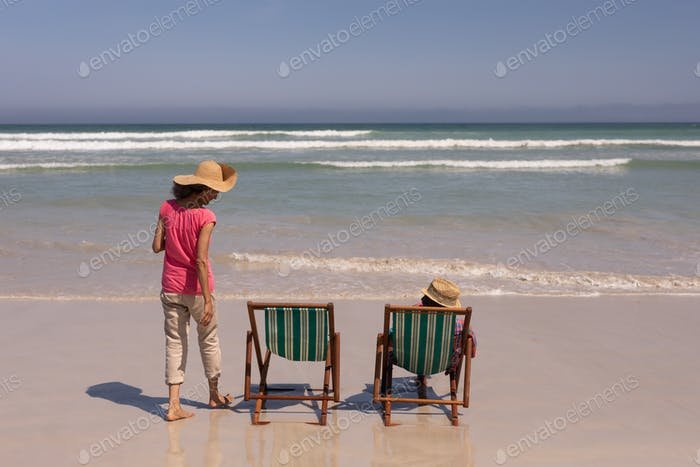 Rear view of senior couple relaxing on sun lounger on beach in the sunshine