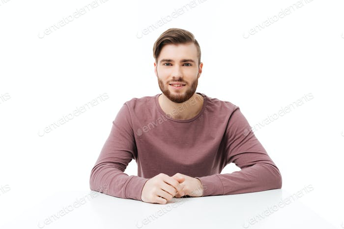 Handsome young and friendly man looking at the camera sitting at the table isolated