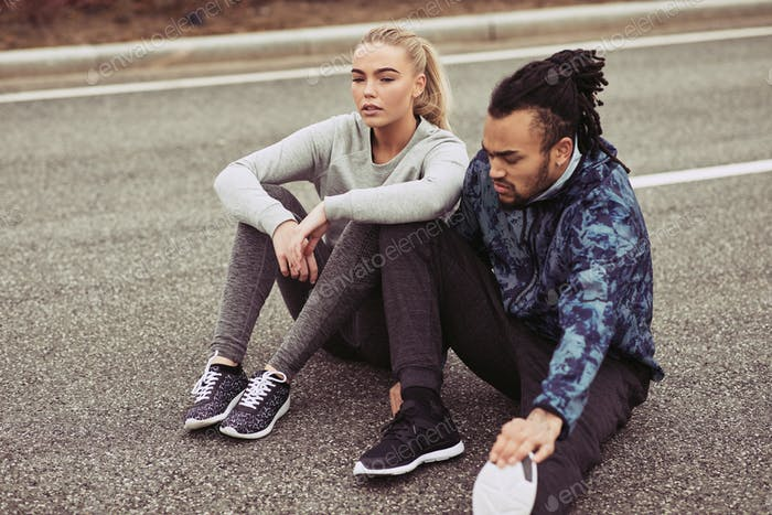 Young couple resting while out for a run together