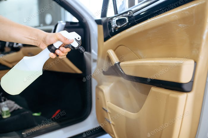 Worker sprays car door trim, dry cleaning