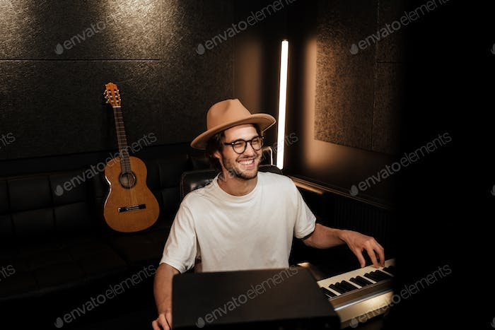 Young handsome musician in hat happily composing new song in modern recording studio